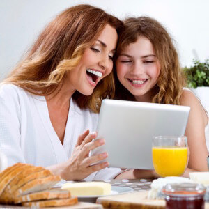 Smiling woman wearing white bathrobe sitting with her daughter at the breakfast table in the kitchen and using a digital tablet together.